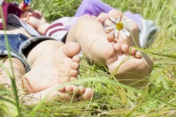 two pairs of children's feet on grass with daisy flower