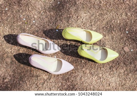 Two pairs of classic pumps shoes, pale yellow and pale pink heels. Classic leather shoes with heels. Woman footwear trends #1043248024