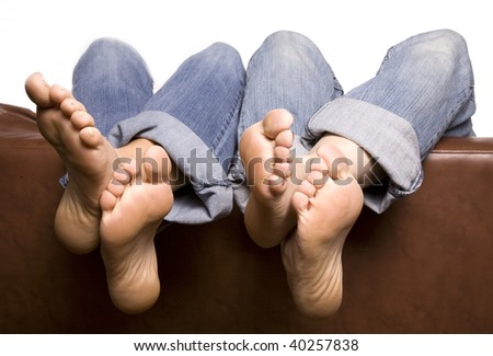 Two pairs of feet with ankles crossed and hanging over the back of the couch relaxing with their jeans rolled up.
