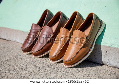 Two pairs of fine genuine leather loafers against a colorful summer color wall. Stock fotó ©