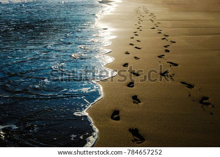 Two pairs of footprints in the sand on the beach and incoming waves