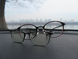 Two pairs of glasses intertwined, resting on a car dashboard with a river view and skyline in the background