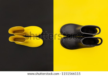 Two pairs of gumboots - yellow female and black male - standing opposite to each other on the inverse backgrounds. Top view. The concept of He and She #1151566115