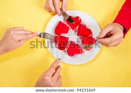 Two pairs of hands are going to eat up jelly hearts from a dish on yellow