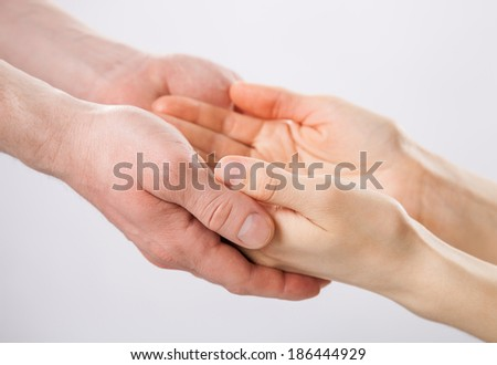 Two pairs of hands holding each other gently