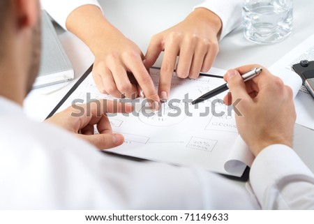 Two pairs of hands passing over business plan