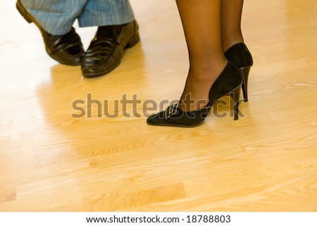 Two pairs of legs, male and female on wooden floor