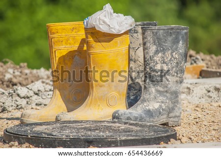 two pairs of old working boots parked on construction site. yellow and black pair used and dirty  #654436669