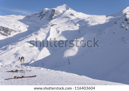 Two pairs of skis, ski lifts and pistes and Hintertux Glacier in Zillertal Alps in Austria at sunset light
