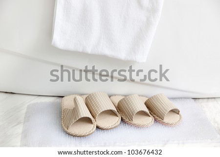 Two pairs of slippers on  bath mat by  the bathtub with towel, a pair for man and another for woman.