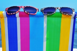 two pairs of sunglasses on a colorful deckchair on the beach