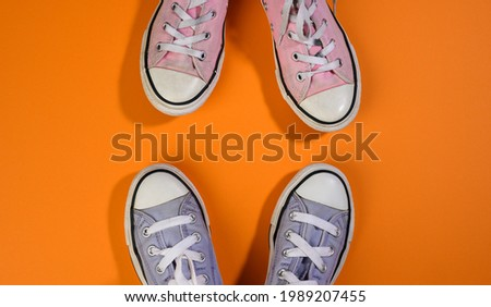 two pairs of textile sneakers on an orange background stand opposite each other. Dialogue and confrontation concept, top view Foto stock ©