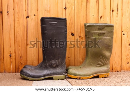 Two pairs of wellington boots against a wooden background - stock photo