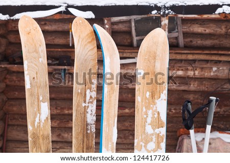two pairs of wide wooden hunting skis and log house wall in winter day - stock photo