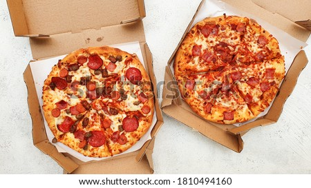 Two pan pizzas in two pizza boxes with their two different flavors is Meatzza and beef delight.