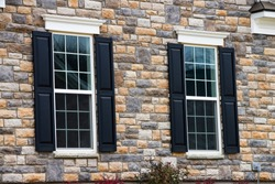 two pane vinyl window with shutters on a vinyl siding house siding