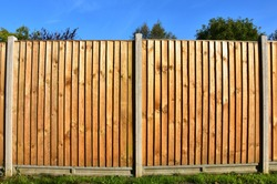 Two panels of a classic wooden featheredge garden fence with concrete support posts