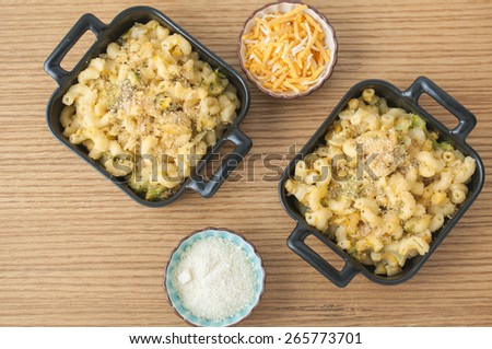 Two pans of macaroni and cheese with broccoli, accompanied by two side dishes of parmesan and cheddar cheese to add