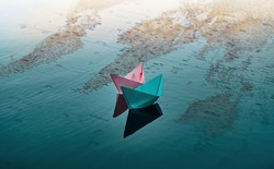 Two paper boats of pink and blue color, float on the water. Under the water you can see a map of the world on which the continents are depicted.