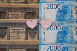 Two paper clips in the shape of hearts on the background of tsarist and modern Russian banknotes