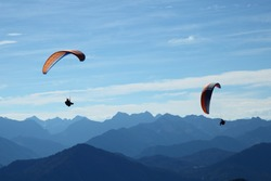 two para-glider flying in blue mountain landscape