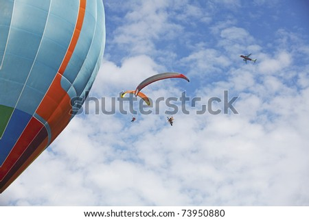 Two paraglider extreme sports parachute gliding past a large colorful balloon with an airplane flying through the cloudy blue sky.