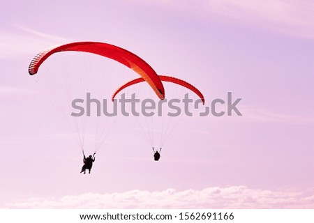 Two paragliders in pink sunset