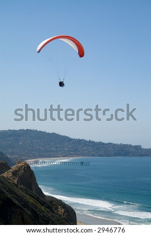 Two paragliders soaring over the Pacific. The city of La Jolla is visible in the background