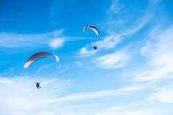 Two Paragliding flying in the blue sky.