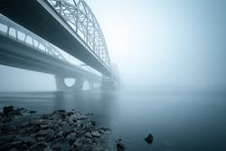 Two parallel bridges over foggy river. Coastal landscape on long exposure. Kiev. Ukraine.