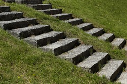 two parallel diagonal lines of stairs on a background of green grass