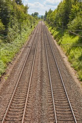 Two parallel railway tracks on a sunny day.