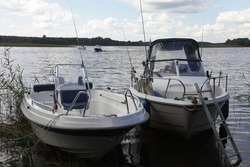Two parked motor boats near river bank on far shore with green trees background on horizon, Volga river calm water at quiet summer day on blue sky background, Russian river landscape, boating tourism