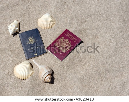 two passports australian/aussie and english/british on a sandy central american tropical beach surrounded by sea shells