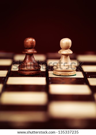 Two pawns chess pieces on a chessboard, concept