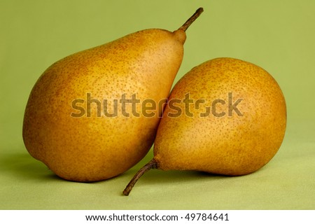 Two pears isolated on light green background