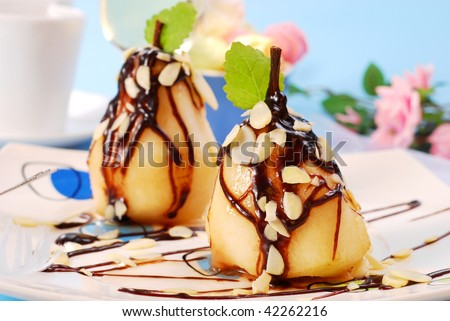 two pears with flaked almonds poured chocolate sauce