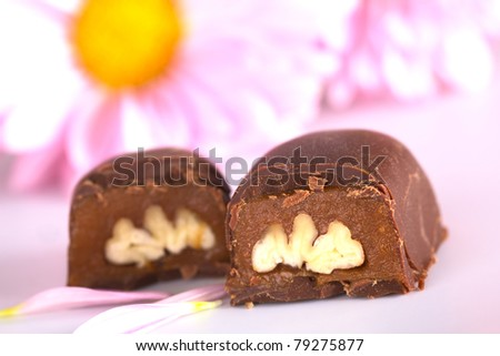 Two pecan nut truffle halves with pink flowers in the back (Selective Focus, Focus on the front upper corner of the right truffle half) - stock photo