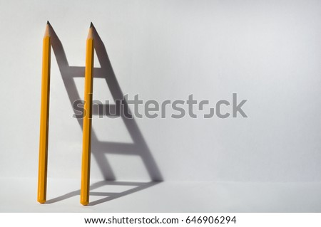 Two pencils and a shadow in form of ladder. Success, teamwork and solving problems business concept. Copy space for text .