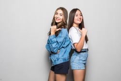 Two pensive young girls dressed in summer clothes standing back to back and pointed each other over gray background