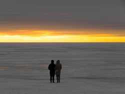 Two people a man and a woman look at the winter sunset under a heavy leaden sky as if it were the end of the world