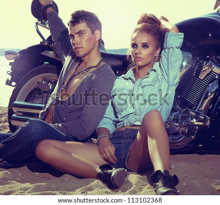 Two people and bike - fashion woman and man sitting by motorbike and resting. Adventure and vacations concept