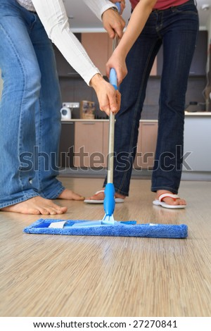 Two people are cleaning the house with one and the same mop