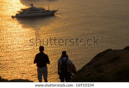 Two people are enjoying sunset at cape Sounio in Greece.