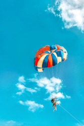 two people are flying on a Colored parachute against a blue sky with huge white clouds.Skydiving is a dangerous sport.A strong wind carries paratroopers through the air.Fearless people soar.vacation