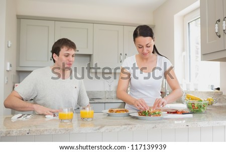 Two people are in the kitchen while one of them makes sandwiches