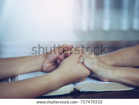 Two  people are praying together over holy bible on wooden table  #717470332