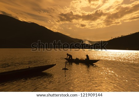 two people are sailing in sunset