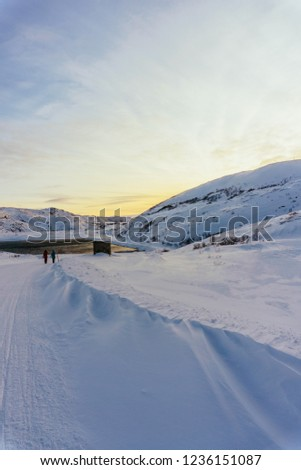 two people are walking in the distance along a snowy winter road in the village beyond the Arctic Circle to meet bright sunset light and a small sea bay