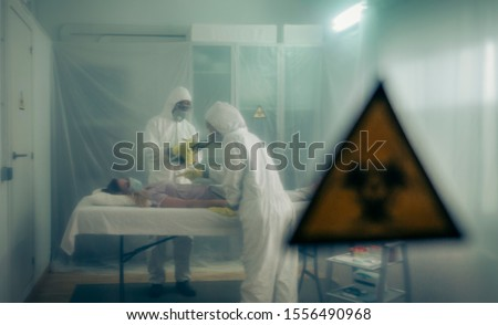Two people attending to a woman with a virus lying on a stretcher in a field hospital with bio hazard symbol in the foreground